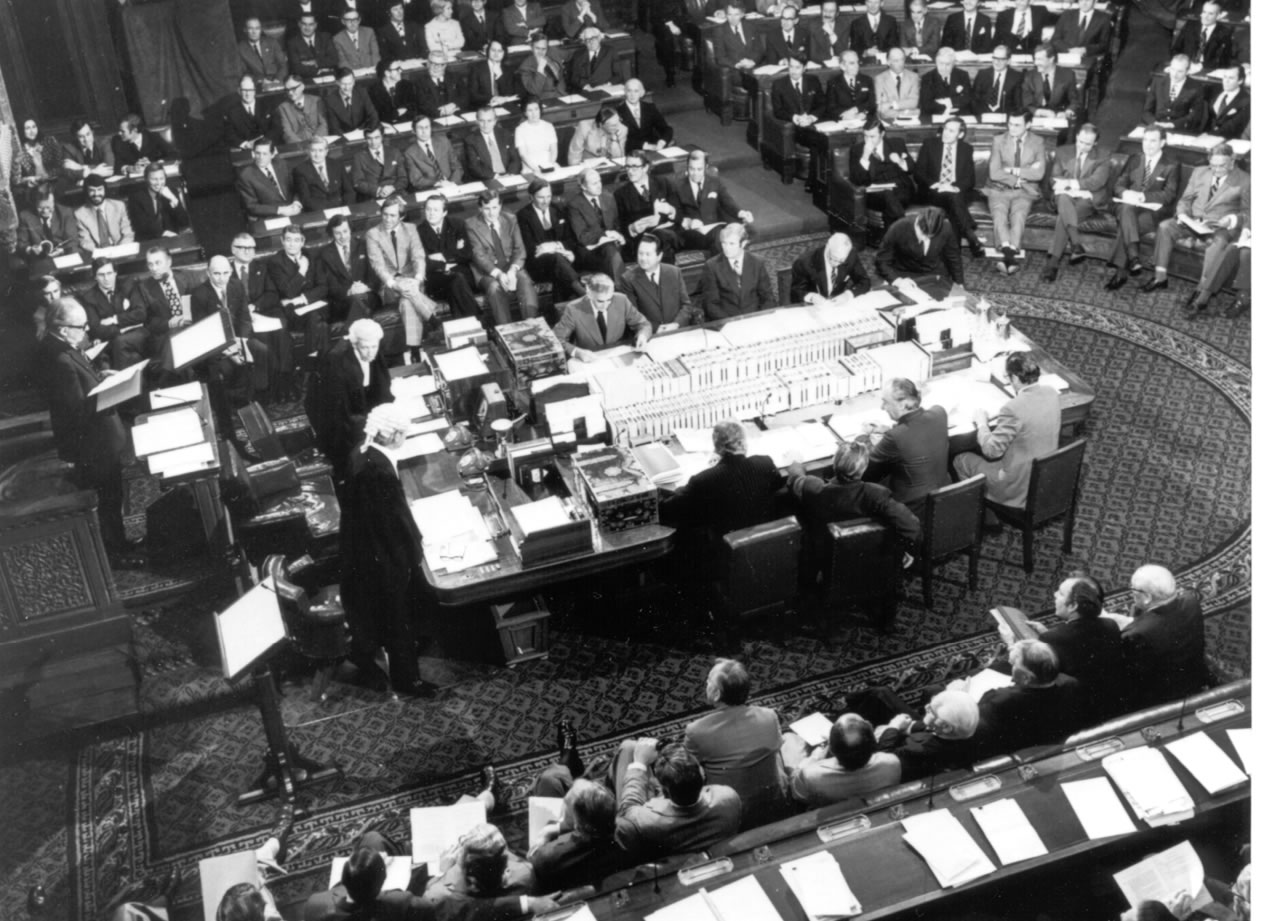 A black and white photo showing the historic joint sitting of both houses of the Australian Parliament in the House of Representatives Chamber, 1974.