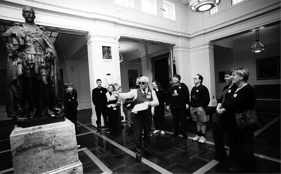 A photo showing a guide explaining the discolouration of the bronze statue of King George V to a tour group in King's Hall.