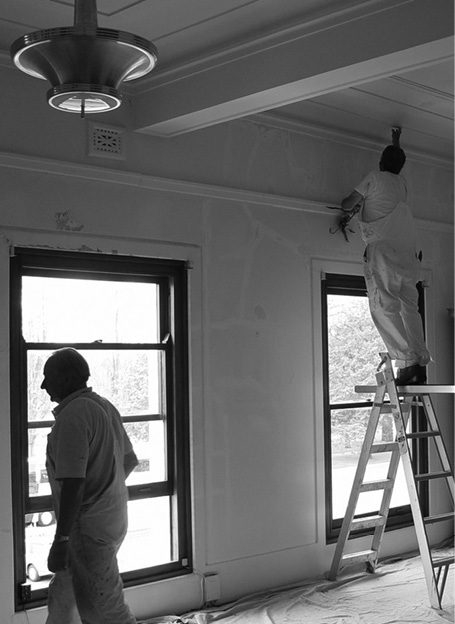 a black and white photo showing painters at work in the Government Party Room, 2004.