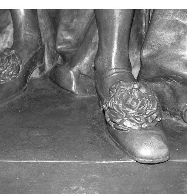 A black and white photo of the left shoe of the bronze statue of King George V.